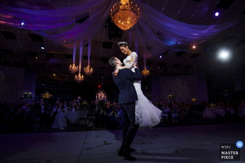 The groom lifts the bride on the dance floor during their colorful greek wedding in Denver at the Seawell Ballroom