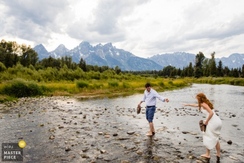 Grand Teton National Park Wedding Day Image of the bride and groom crossing a stream