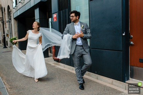 Canada wedding photo from Old Montreal of the Groom accidentally pulling bride's veil as they walk together and he touches his new wedding ring