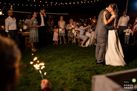 Canada wedding photography from Montreal, Quebecof the Wedding couple dancing at night as guests hold sparklers