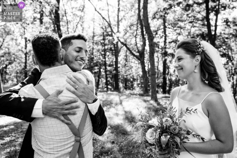 Outdoor wedding photography from Mont Royal Park, Montreal of the Groom being hugged by cousin as bride watches during a micro wedding