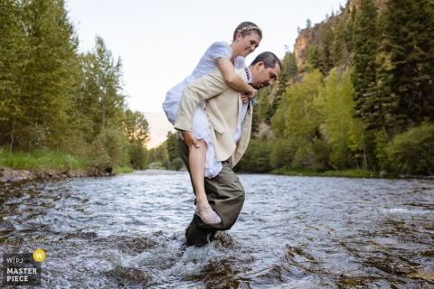 MT wedding elopement photo from Rock Creek, Montana as the groom carries bride through water to ceremony