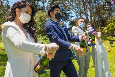 N. California wedding photo from outdoors at the Golden Gate Park San Francisco of Two brides and two grooms popping champagne after their double wedding ceremony