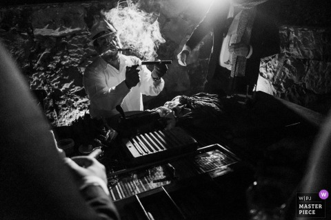 Outdoor, night wedding photography from San Miguel de Allende Instituto, Guanajuato, Mexico as A cigar maker smokes and lights a guest's cigar during the reception