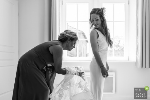 Wedding photography from Château de Romécourt, France showing the Bride's mother is adjusting her dress' train