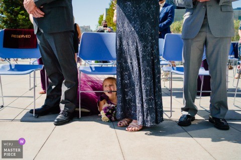 The Cathedral of Christ the Light Outdoor Ceremony image of flower girl biting chair during ceremony