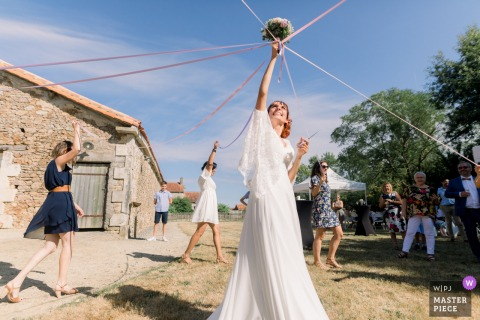 FR outdoor wedding photo from Domaine de la Gerberie, Vendée of the Game of the wedding ribbons during a wedding reception in the french countryside