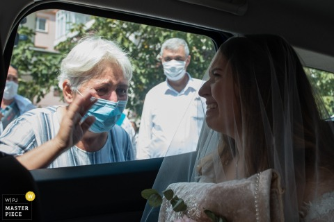 Luleburgaz Wedding Photography | Bride cries in car as the old relative wearing a covid-19 mask waves her goodbye outside the window