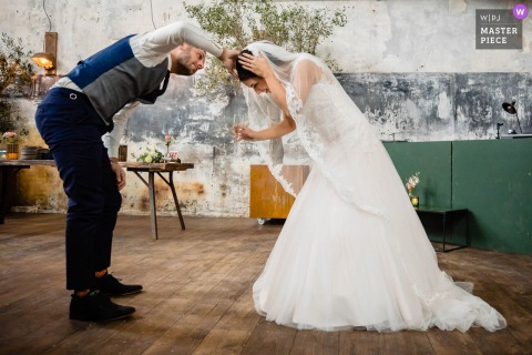 Netherlands Wedding Photo | The groom tries to fix something on the bride's head, after the ceremony