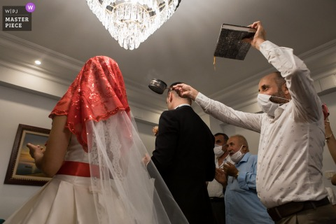 Igdir, Turkey Wedding Photography | Man holding Koran hovering incense over bride and groom's heads
