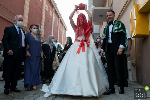 Bride raises a jug before throwing it to the ground to break it. Breaking a jug is a Turkish wedding tradition still performed in many Anatolian weddings