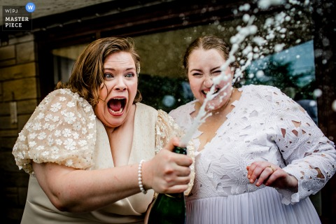 Brides react to a bottle of champagne spraying at their backyard wedding in New Lenox, IL