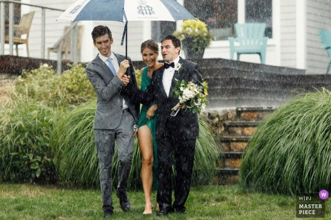 Marion MA wedding photo of groom and friends walking under pouring rain