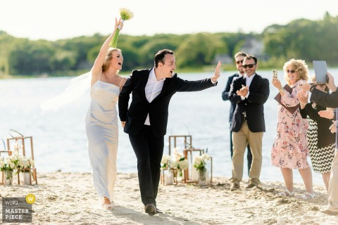 Outdoor wedding photography from Osterville MA - Dowses Beach of the Bride and Groom walking down the isle and greeting their virtual guests
