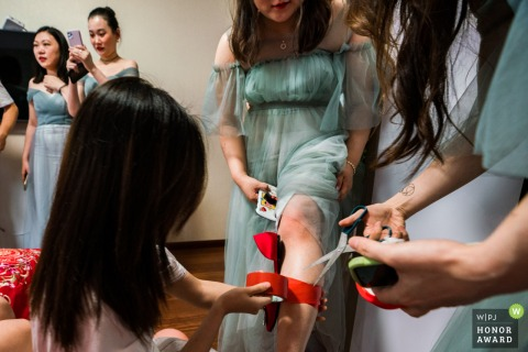 Fujian wedding photography of The bridesmaids tying wedding shoes on their legs to hide the wedding shoes under their skirts