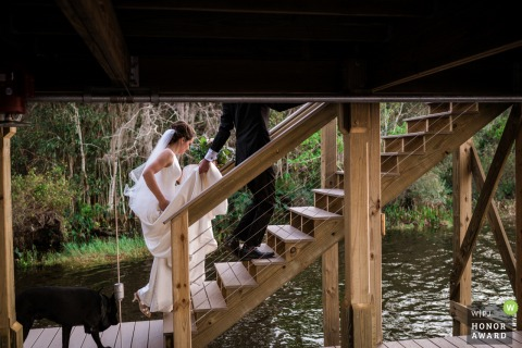 Florida photography from a backyard wedding, private home, Orlando of the Bride and Groom walking up to the top of the deck after their ceremony