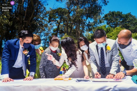 California outdoor wedding photo from Golden Gate Park, San Francisco of Newly-wed couple signing their marriage licenses with witnesses
