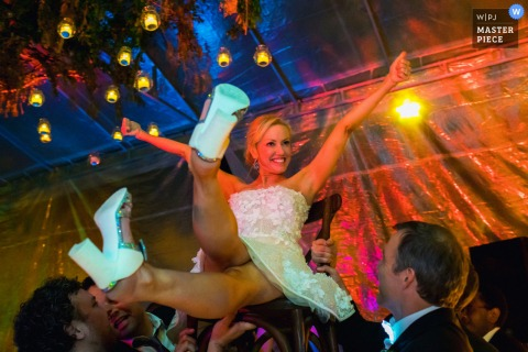 Fun wedding photo at Casa Chorro, San Miguel de Allende, Mexico of The bride lifted on a chair at her wedding reception