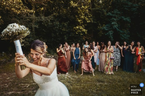 Outdoor wedding photo from Il Conventino di Mentana, Roma of the tossing Bouquet gathering