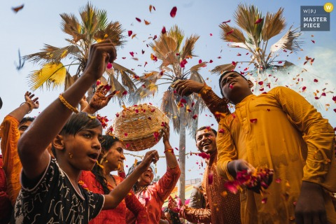 wedding photo from Ahmedabad, India showing the tossing in the air of the Holi flower