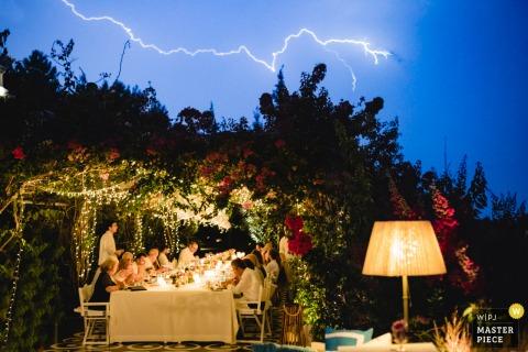 Maçakızı博德魯姆/土耳其別墅的閃電戶外婚禮照片,顯示婚禮客人在雨天的晚餐