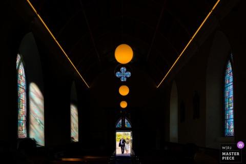 來自愛爾蘭弗吉尼亞州的婚禮照片,顯示新娘和爸爸以光亮的姿態到達一個空曠的鄉村教堂參加14人的婚禮