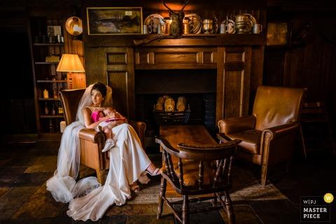 """在愛爾蘭威克洛的布魯克洛奇酒店的IE婚禮照片,一個""""被午睡困住""""的新娘看著自己的雞尾酒時間,因為她的孩子在她的懷裡小睡"""