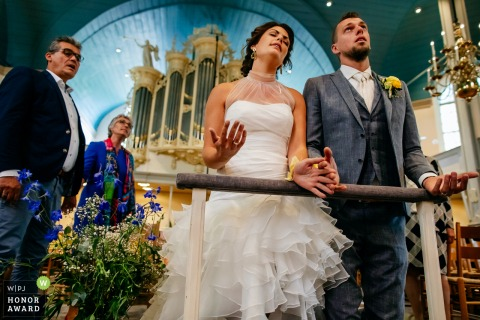 Wedding photography from the church, sliedrecht, netherlands of the bride and groom worshipping during the ceremony