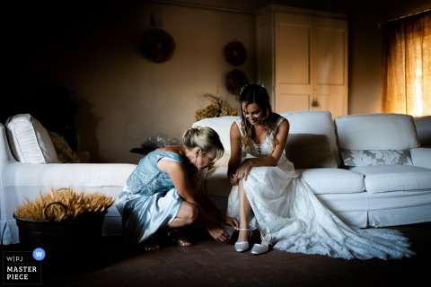 wedding photography image from Villa Podernovo di Monticiano, Siena, Italy of The Bride's mother helping the daughter to wear shoes