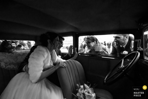 Mantova, Italy Wedding Image | While the bride and groom await the arrival of the driver, the couple's closest friends approach for a greeting