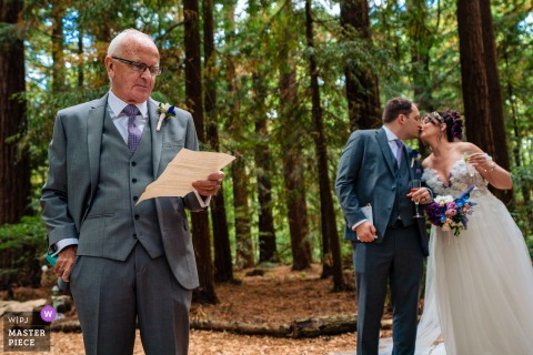 Outdoor ceremony wedding photography from Two Woods Estate, West Sussex showing the Bride & Groom having a kiss, while Dad reads his speech