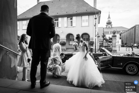 wedding photography from the City hall Brumath, France of the bride arriving by a convertible car