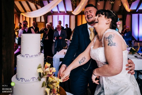 Wedding Reception Reportage Image from Brookfield Barn, West Sussex created as the Couple bursts out laughing while cutting cake