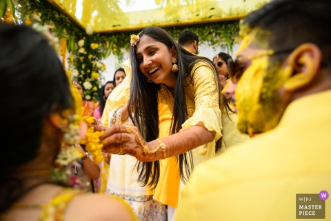 wedding photography from Mumbai, India during the haldi ceremony - brings out some of the best reactions Capturing the action and reaction together is the key