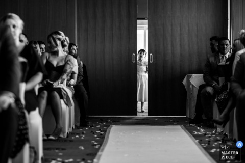 Wedding ceremony image In York, UK showing A flower girl peeks through the doors just before a wedding ceremony begins