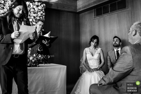 Wedding reportage photo from England of the ceremony showing A bride and groom fighting back tears during a reading - the reader's stance mirrored by the celebrant