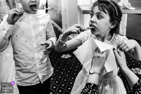 Kids wedding photography from England at the Reception venue of Two young wedding guests enthusiastically enjoy some canapés as a mother struggles to fit a napkin to the little girl, perhaps a little late