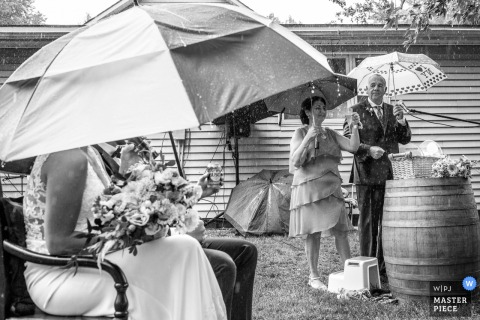 Outdoor wedding photography from a Backyard ceremony in St. Thomas, Ontario, Canada showing The speeches carry on during a downpour of rain with umbrellas