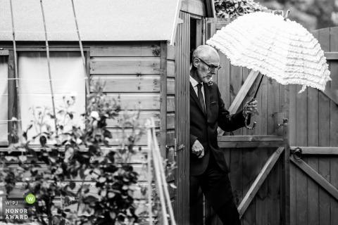 UK, Hertfordshire, Parents Home reportage de mariage image d'un père sortant d'un hangar juste avant le service