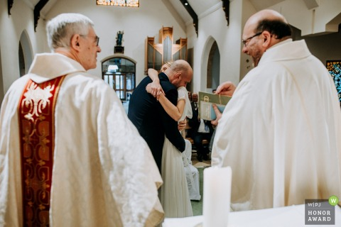 England Church wedding reportage photography created as a couple embraces after their first kiss as two priests - one English and one Polish - chat and laugh together in the foreground
