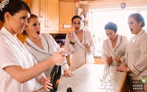 Carlow, Irland Brautjungfern, die Champagner in diesem Hochzeitsreportagefoto öffnen