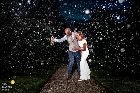 wedding photography from Kasteel Maurick in Vught of The wedding couple popping the champagne
