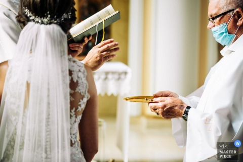 wedding photography from the Parish of the Blessed Virgin Mary in Kalisz, Poland of The masked minister handing the priest rings on a tray.