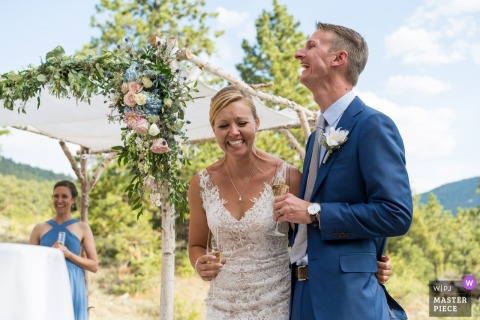 wedding photo from outdoor ceremony in Estes Park, CO of the Couple laughing during toasts