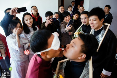 Wedding photography from Fujian, China of the gate crashing game with blindfolds and lipstick