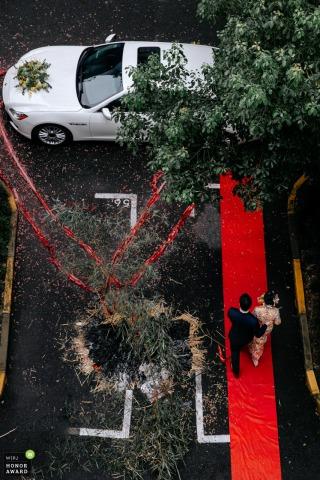 Hochwinkel-Hochzeitsfotografie von Fujian, China, die den roten Teppich und die Limousine zeigt