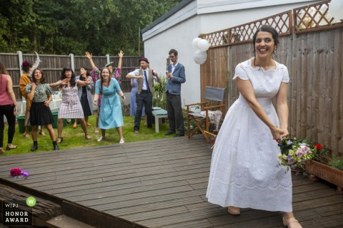 East London bride Throwing the bouquet in this wedding reportage photo