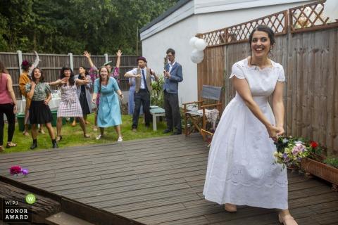 Mariée de l'Est de Londres jetant le bouquet dans cette photo de reportage de mariage