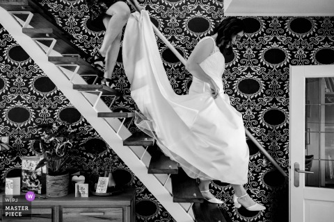 Netherlands bride descends the stairway at home as she prepares to leave for the wedding ceremony