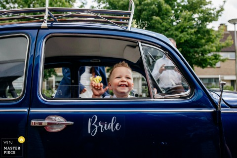 Netherlands wedding photography of a kid in a wedding car with a sign 'bride'